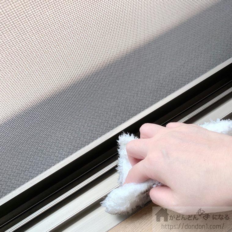 窓のサッシを拭いている